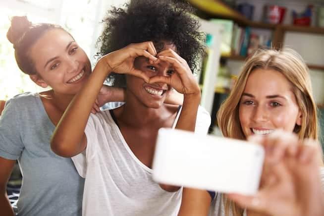 Three Female Friends Taking Selfie Whilst Making Breakfast