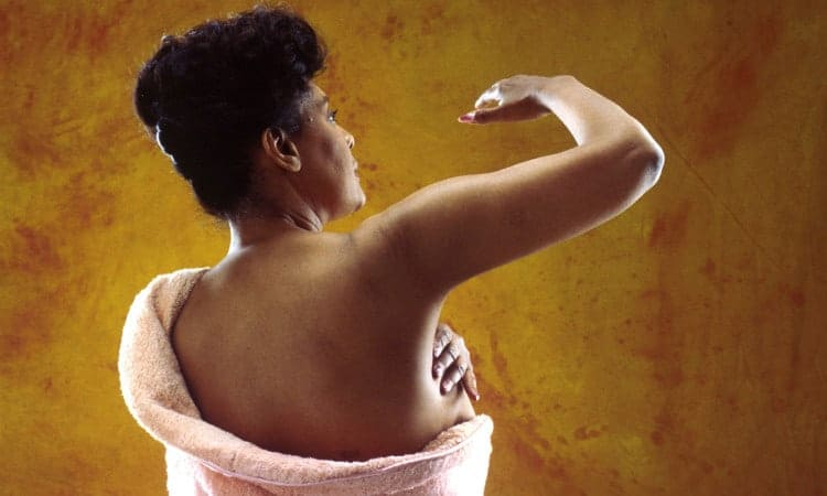 A woman performs a breast self-examination.